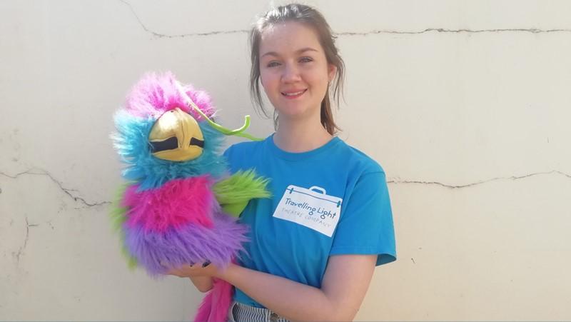 young female wearing blue t-shirt holding a bird puppet