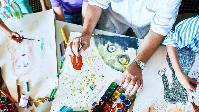 adult and children drawing and painting. Arial shot of hands and art work
