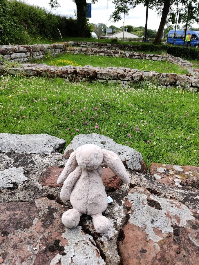 toy rabbit sitting on a low stone wall