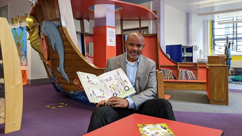 Marvin Rees, Mayor of Bristol sitting in library holding a book